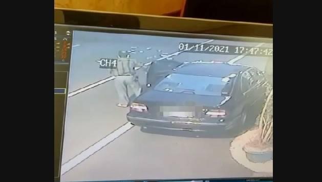 吳姓工程包商從車內抱出90多萬元現金,剛好一陣強風吹來,將手中一堆千元大鈔吹落一地。(記者李立法翻攝)