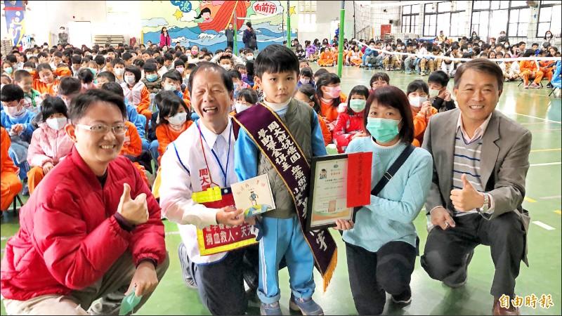 勝利國小一年級的吳恩宇(中)昨天在媽媽(右二)陪伴下獲頒周大觀獎學金。(圖右一為勝利國小校長李國政、左二為周大觀文教基金會創辦人周進華、左一為癱瘓工程師賴志銘)。(記者羅欣貞攝)