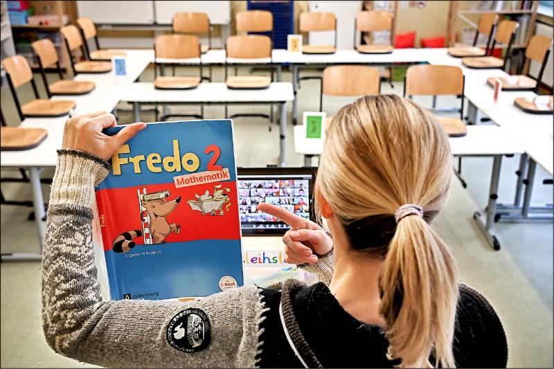 為減緩武漢肺炎傳播,德國境內學校上月十六日起關閉至今。圖一為北萊茵—西發利亞邦韋瑟爾郡丁斯拉肯市一名小學老師,十八日在空無一人的教室中,使用平板電腦對在家上課的學童進行教學(歐新社)