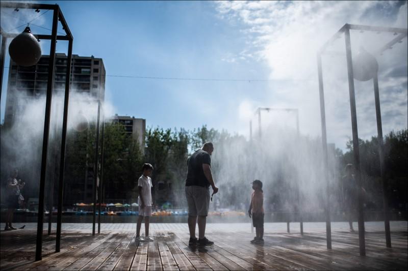 去年8月間法國巴黎民眾在一處灑水處消暑。(法新社資料照)