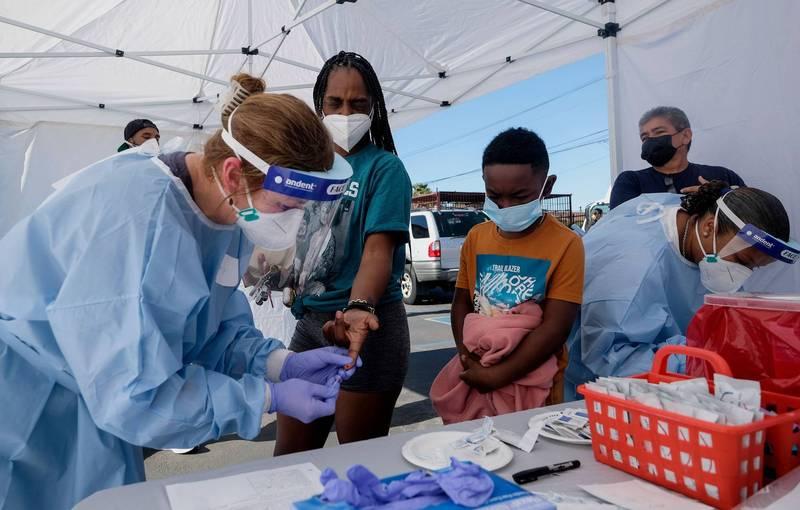 美國加州洛杉磯的醫護人員,18日為民眾做血液篩檢。(法新社)