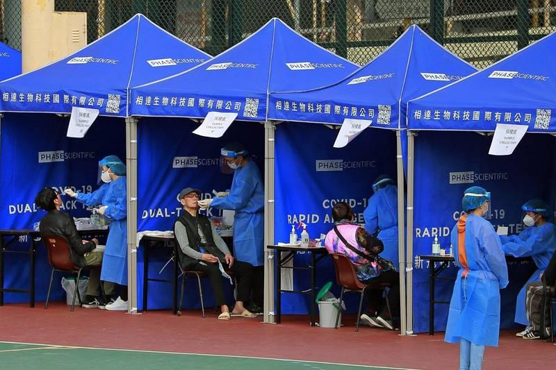 香港今天宣布新增77例武漢肺炎確診病例,均為本土感染病例,其中41人住在油麻地、尖沙咀和旺角地區(簡稱油尖旺區)。此外,今天有60多例一採陽性,其中約10例也來自油麻地。圖為香港臨時設置的武漢肺炎篩檢站。(美聯社)