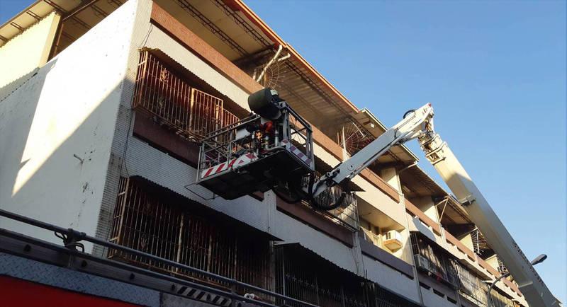 消防人員用雲梯車救出在陽台等待救援的3人。(圖由南投縣消防局提供)
