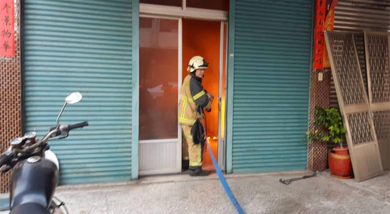 草屯市區的這間民宅起火點在一樓,火光熊熊,防隊員拉水線滅火。(圖由南投縣消防局提供)