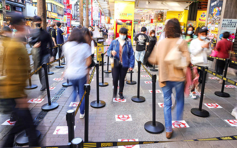 Customers at Japanese discount chain Don Quijote maintain social distancing and wear masks at the store in Taipei yesterday. Photo: CNA