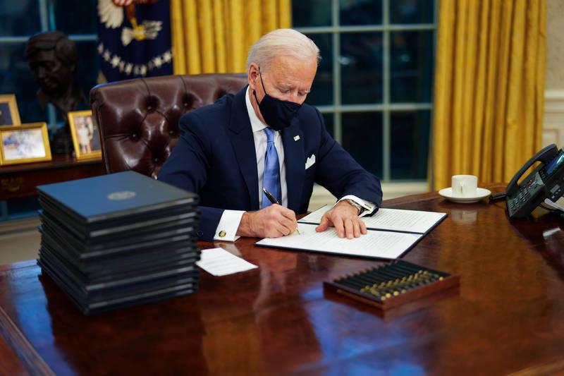 拜登就職後立即簽署17項行政措施,推翻多個川普時期的重大決策。(彭博)