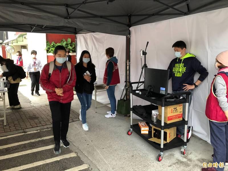 大學學科能力測驗今天登場,受到疫情影響,考生都要量測體溫,並且佩戴口罩進入考場應試。(記者俞肇福攝)