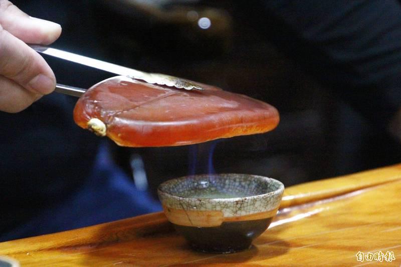 林篤毅用高粱浸泡烏魚子,用高粱烘烤烏魚子。(記者林宜樟攝)