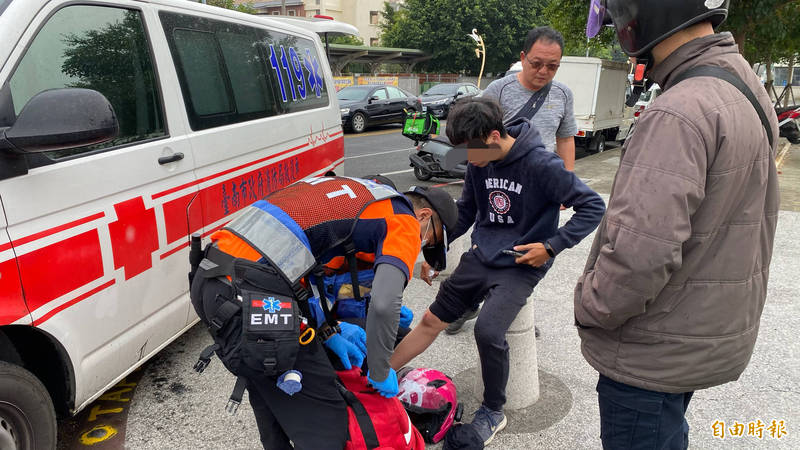 新營消防隊救護員檢查外送平台人員吳男的傷勢。(記者楊金城攝)