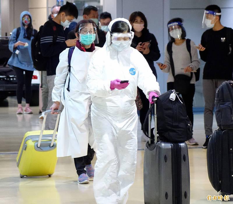 海外台人提前返台居家檢疫過春節,不少旅客穿防護衣、戴護目鏡。(記者朱沛雄攝)