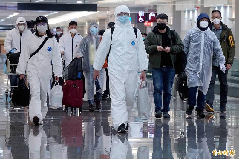 不少旅客穿著防護衣、戴護目鏡返台,做好防疫保護措施。(記者朱沛雄攝)
