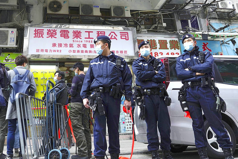 Police officers stand guard outside the office of lawyer Daniel Wong in Hong Kong on Thursday last week as police conduct a search. Photo: Vincent Yu, AP