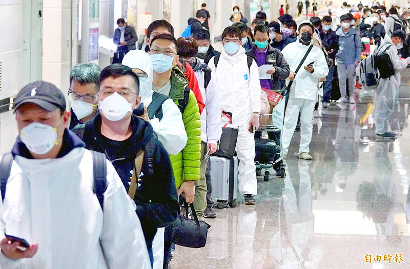 People returning home to complete quarantine in time to celebrate the Lunar New Year with their families arrive at Taiwan Taoyuan International Airport yesterday. Photo: Chu Pei-hsiung, Taipei Times