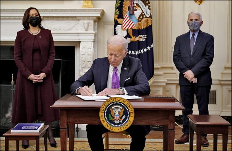美國總統拜登二十一日在副總統賀錦麗(左)、國家過敏與傳染病研究院主任佛奇(右)陪同下,簽署十項行政命令加強防疫措施。(法新社)