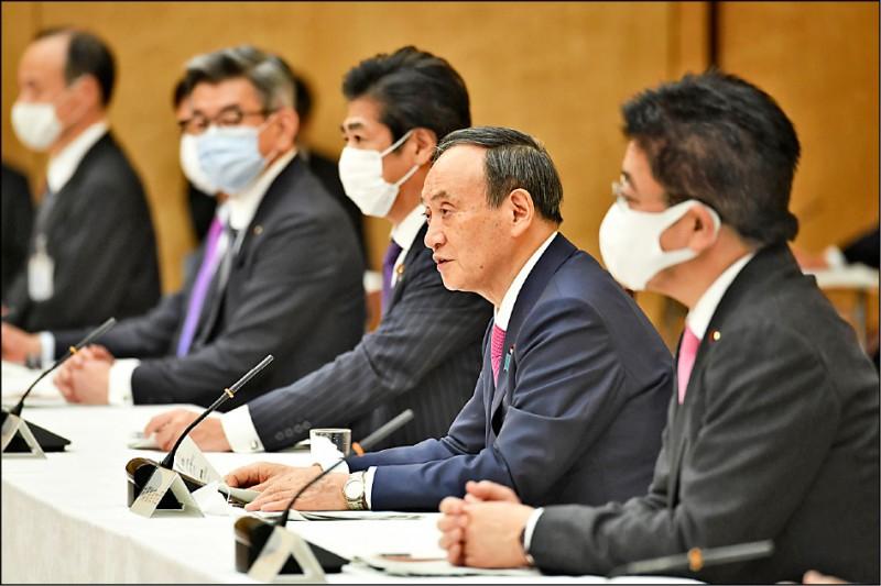 日本首相菅義偉(圖中未戴口罩者)二十二日主持內閣會議,他就武漢肺炎疫情控制問題強調,最快二月底就可以展開疫苗注射。(美聯社)