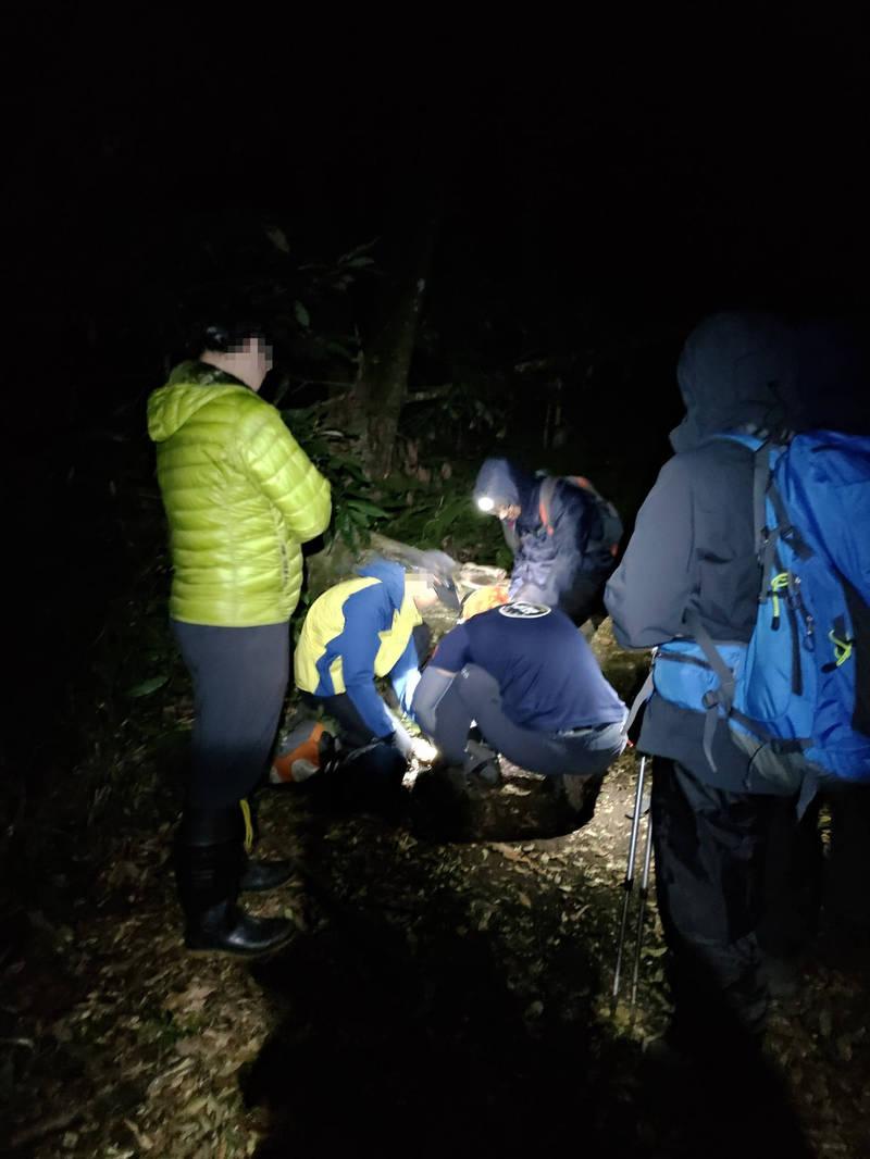 南投縣消防搜救人員晚間近8點接觸到受傷登山客,為他包紮及固定受傷部位。(南投縣消防局提供)