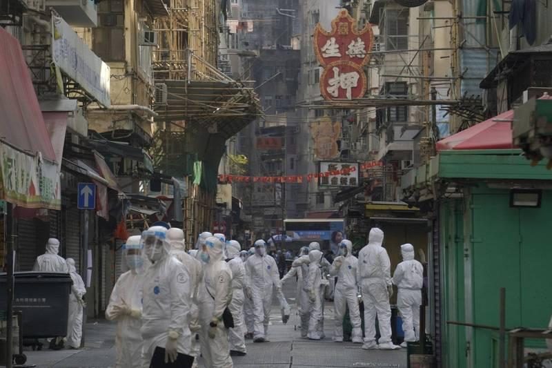 香港爆發疫情滿一週年,官方今天通報新增81例確診,累計確診數破萬例。港府凌晨起對部分區域進行封區後,下午再通報將6棟大樓納入強制檢測範圍。(美聯社)