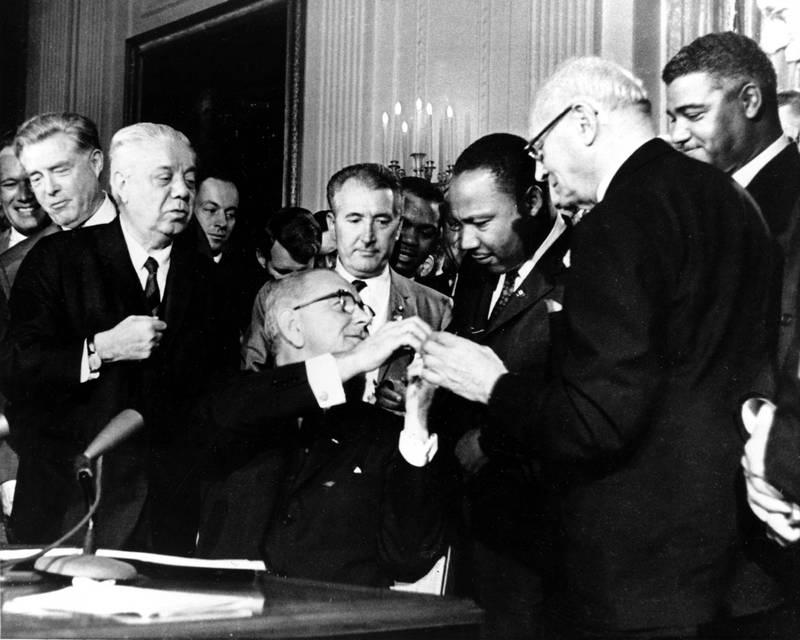1964年民權法案通過時,詹森(中)贈筆金恩博士(右3)。(美聯社)