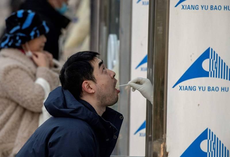 北京某些醫療機構日前被北京市民舉報拒診來自中、高風險地區的病患,北京市衛健委今天證實這項消息。(圖為北京民眾今天檢驗站篩檢武漢肺炎一景。(法新社)
