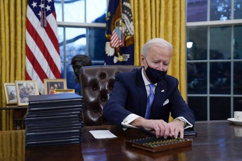 拜登剛開始簽署行政命令時,眼前有一整盒簽字筆。(美聯社)