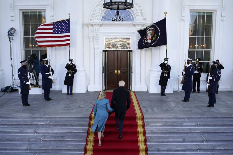 美國總統拜登20日在就職典禮後,在奏樂聲中走上白宮北門廊(North Portico)的台階。(美聯社)