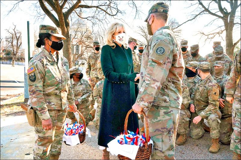美國第一夫人吉爾當天向在國會山莊外休息的部隊分送餅乾慰問。(法新社)