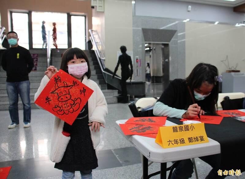 龍泉國小書法展開幕,書法班學生現場揮毫寫春聯,民眾踴躍索取。(記者歐素美攝)