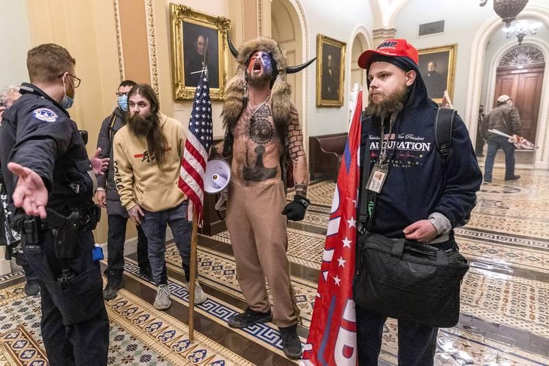 錢斯利6日衝進國會大廈時由於赤裸上身露出刺青,頭戴牛角熊皮帽,鮮明形象讓他在各大媒體報導及社群媒體中十分顯眼。(美聯社)