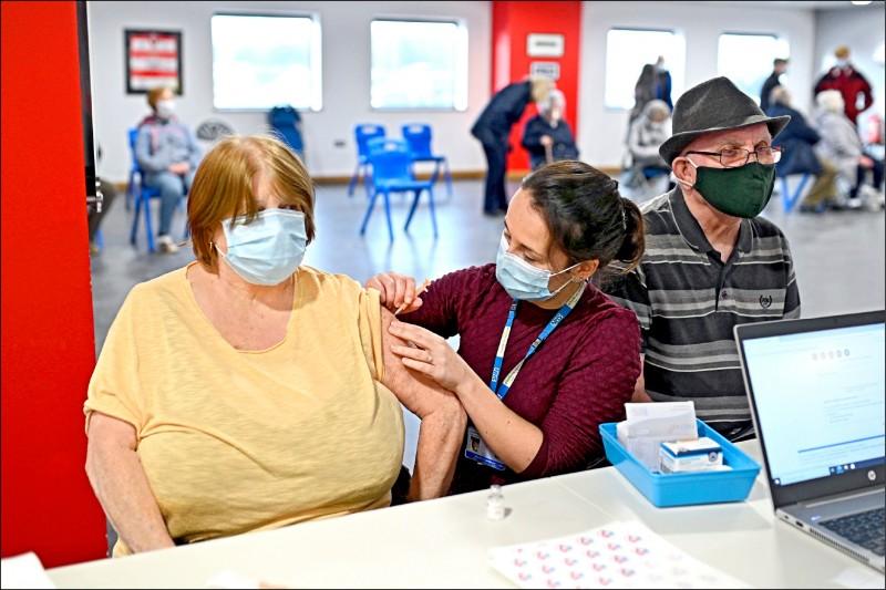英國政府為了讓更多民眾接種疫苗,將兩劑疫苗的施打間隔從三週延長至十二週。圖為英格蘭頓卡斯特被當成暫時疫苗接種站的體育場內,二十三日一名婦人正在接種疫苗。(法新社)