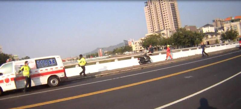 男子坐在橋面扶手上,險象環生。(記者許國楨翻攝)