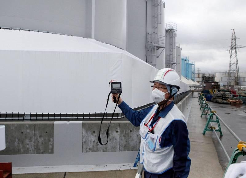 日本福島核一廠2號及3號機組廠房放射線量仍高得能讓人在數小時內致命,東京電力公司預定2022年開始取出反應爐中熔化核燃料等廢爐作業恐因此順延。圖為東京電力人員在電廠放射廢水儲槽外測量放射線。(路透)