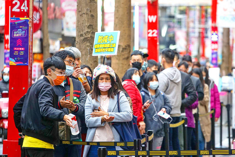 Customers line up outside Japanese retailer Don Don Donki in Taipei's Ximending area yesterday. The store was implementing disease prevention measures to prevent any possible spread of COVID-19. Photo: CNA