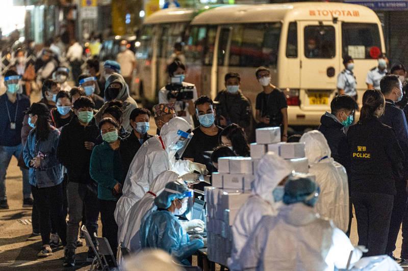 香港昨新增64例確診,強制檢測39幢大樓。圖為油麻地禁區內排隊領取物資的居民。(彭博社)