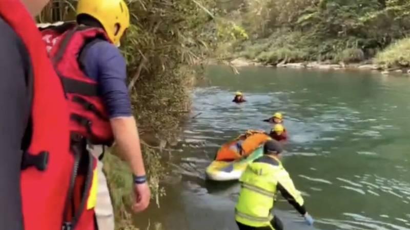 一名女獨木舟愛好者在基隆河上游淺水區,搬運獨木舟時,被同伴發現溺水,消防員協助將躺在獨木舟上的女愛好者後送就醫。(記者林嘉東翻攝)