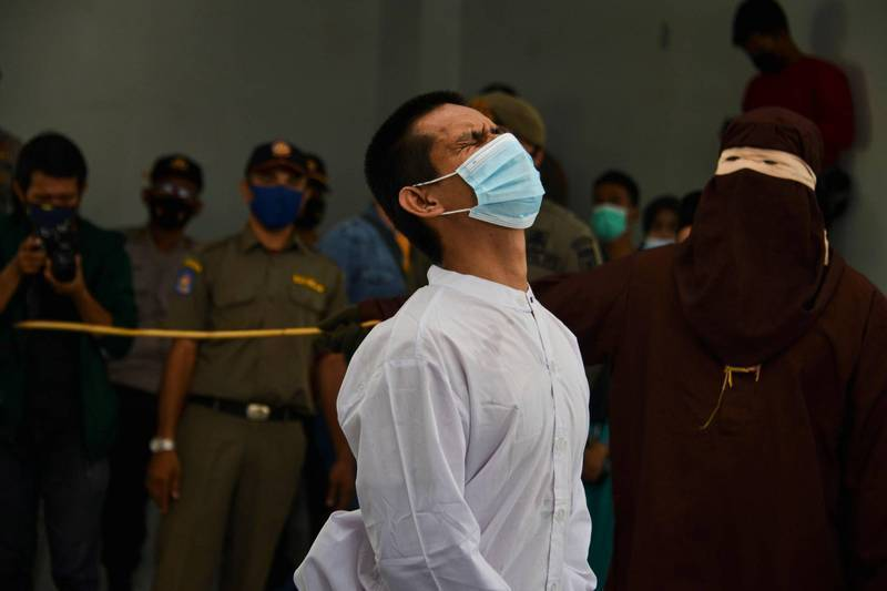 印尼亞齊特區28日公開一對男同志情侶執行鞭刑,每人打77下。(法新社)
