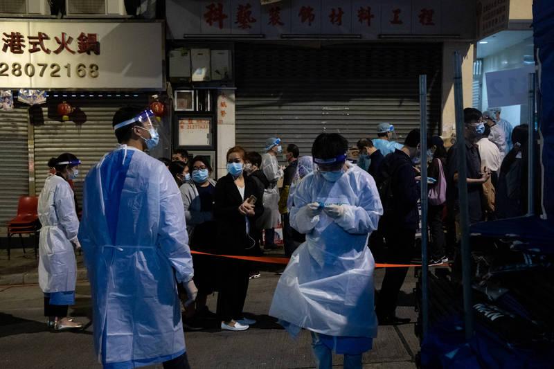 香港增28例確診,11座大廈污水驗出陽性,機場工地也爆發群聚感染。圖為排隊接受檢測的居民。(彭博社)