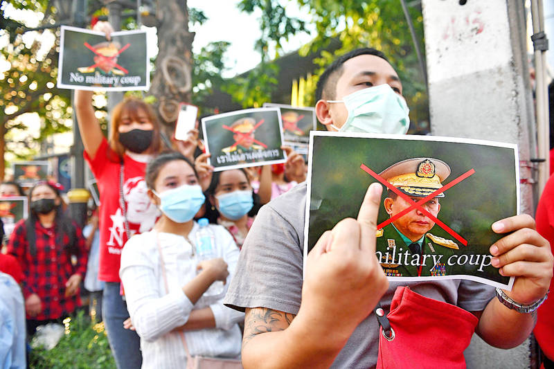 Burmese migrants hold up posters of Myanmar Commander-in-Chief of the Defence Services Min Aung Hlaing as they take part in a demonstration outside the Myanmar embassy in Bangkok yesterday. Photo: AFP