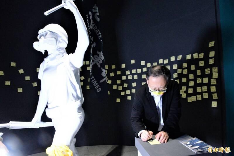 高雄市副市長史哲在參觀「若水,如火,有聲」特展後,寫下「不能放棄、不能忘記」貼於連儂牆上。(記者許麗娟攝)