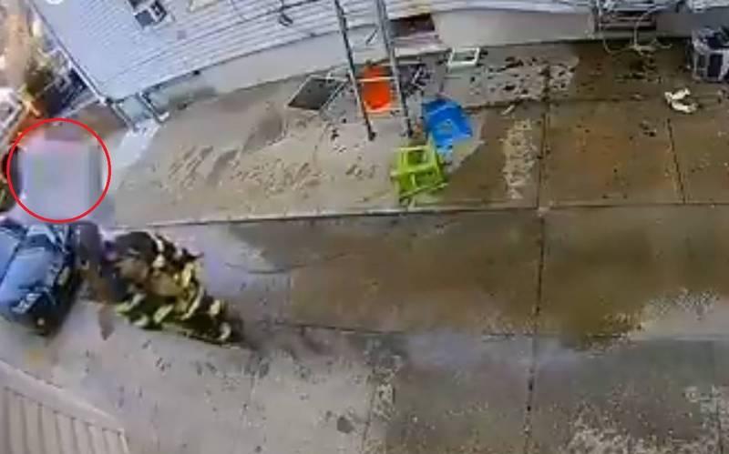 一位消防隊員在場救援時,意外遭一台從天而降的冷氣機砸中頭部。(擷取自推特)