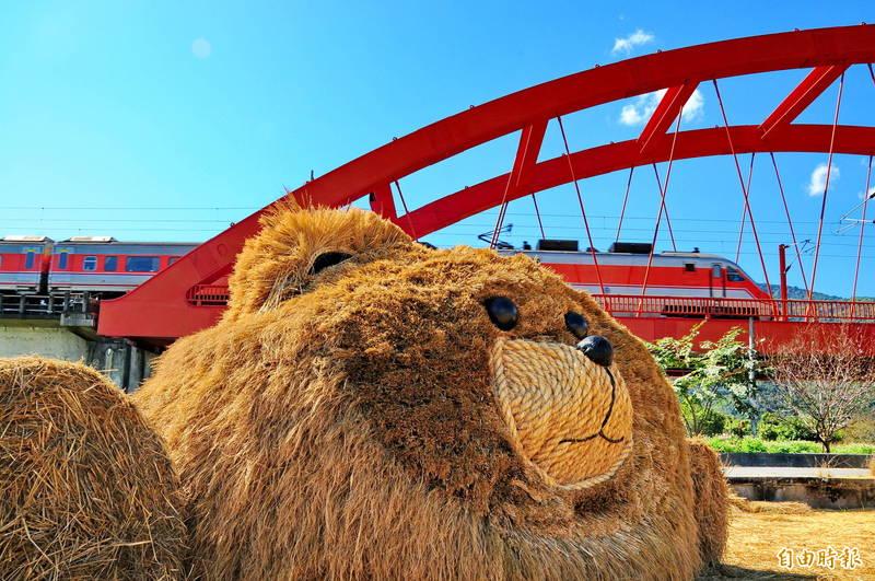 玉里「客城稻草藝術節」,「福氣熊」擁有長輩最愛的大餅臉,圓滾滾毛茸茸看起來就很福氣,牠在鐵路橋邊看著火車來來往往,萌萌的表情若有所思!(記者花孟璟攝)