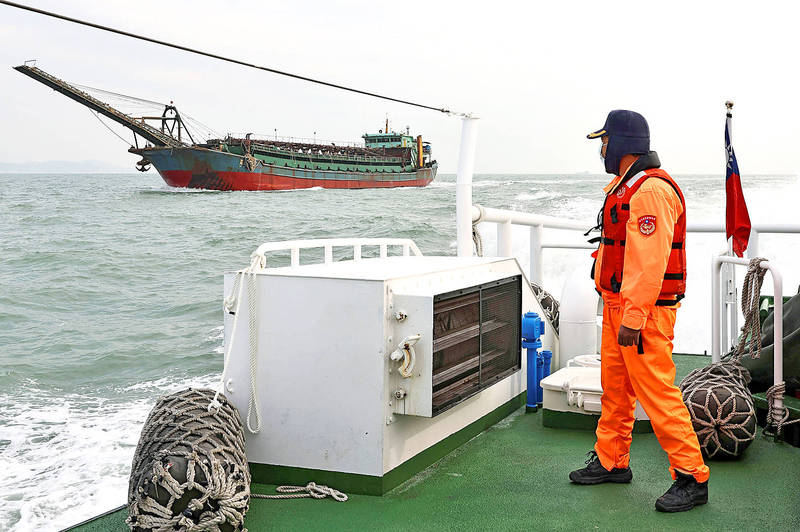 A coast guard looks at a sand dredger with a Chinese flag in waters off the Matsu Islands on Thursday last week. Photo: Ann Wang, Reuters