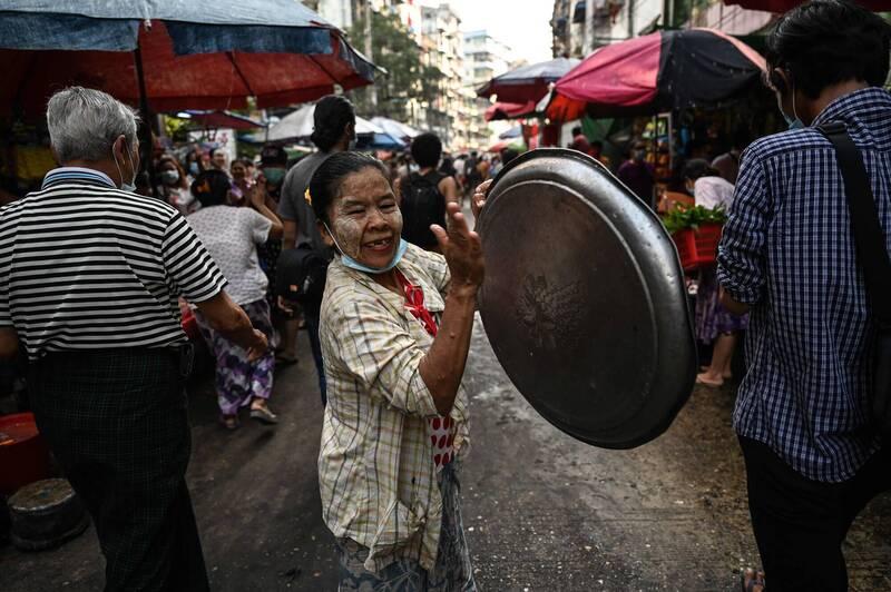 仰光居民敲鍋擊盆鼓勵示威者。(法新社)