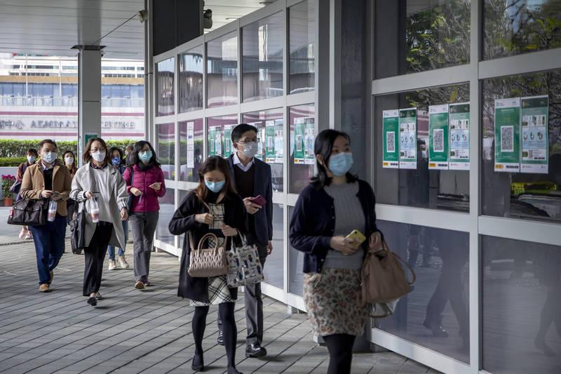香港疫情回溫,今天通報28例為本土案例,其中6例感染源頭不明,當局另懷疑鰂魚涌惠利大廈病毒傳播出現「煙囪效應」。(彭博)