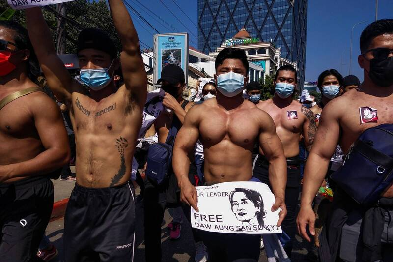 The half-naked hunk held a poster releasing Aung San Suu Kyi.  (AFP)