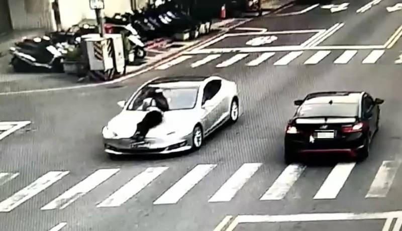吳姓男子趴在特斯拉引擎蓋上(左),被車子載著開了約300公尺遠後平安下車。(記者楊金城翻攝)