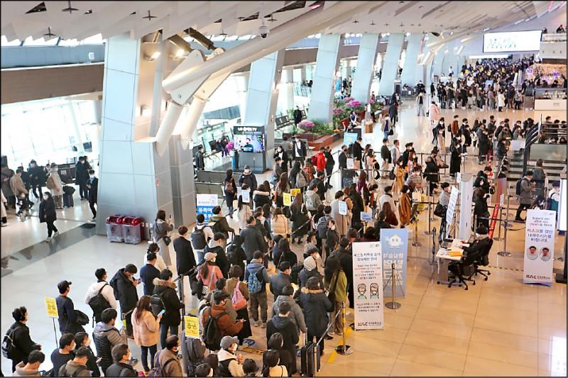 南韓人同樣過農曆年假。圖為11日在首爾金浦機場,許多要返鄉過年的旅客,戴口罩排隊準備登上國內線班機。(美聯社)