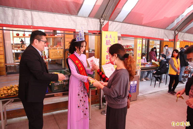 嘉義媳婦阮碧雲(右)與先生高愷村(左)今天發放愛情麵包與香蕉。(記者林宜樟攝)