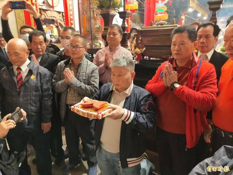 鎮瀾宮董事長顏清標下跪擲筊抽國運籤。(記者張軒哲攝)