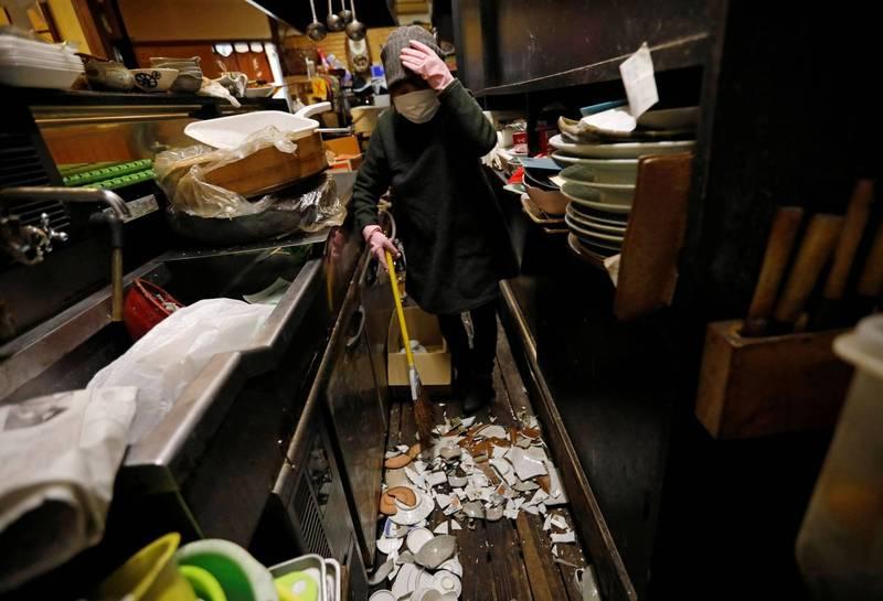 圖為福島縣一間居酒屋老闆正在收拾地震造成的混亂。(路透)