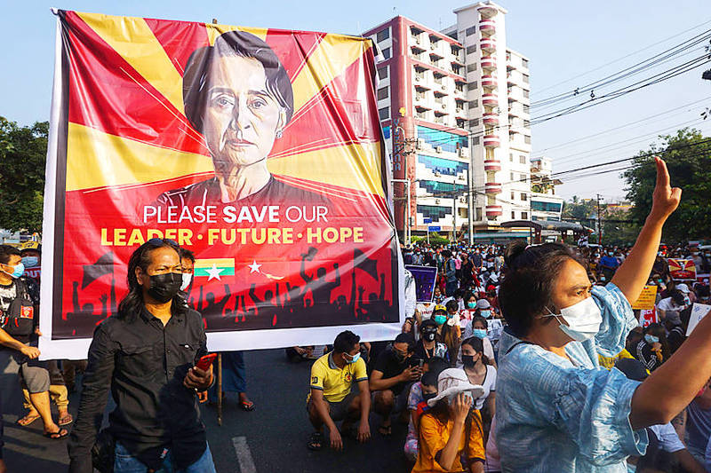 Demonstrators carry a banner featuring an image of Burmese State Counselor Aung San Suu Kyi at a protest against the military coup in Yangon, Myanmar, yesterday. Photo: AP